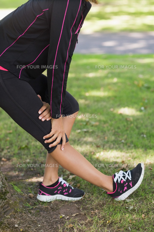 Mid section of woman stretching her leg during exercise at park FYI00485615