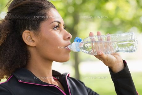 Close up side view of tired woman drinking water in park FYI00485616