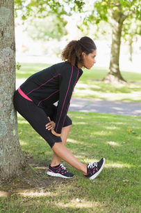 Healthy woman stretching her leg during exercise at park FYI00485619