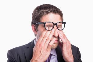 Closeup of a worried businessman rubbing eyes FYI00485745