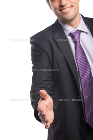 Smiling businessman offering a handshake FYI00485762