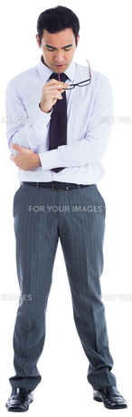 Unsmiling businessman holding glasses FYI00485797