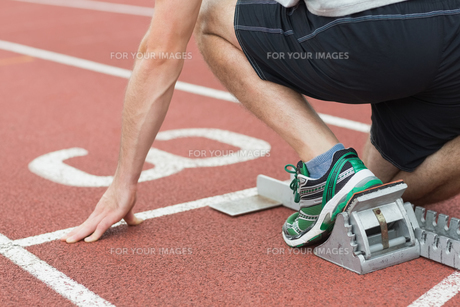Mid section of a man ready to race on running track FYI00485844