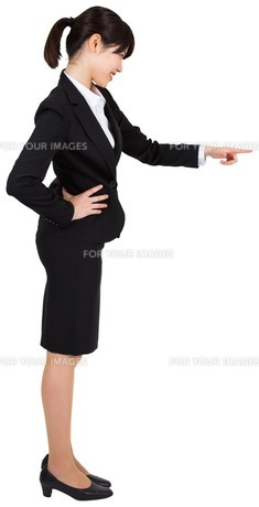 Smiling businesswoman pointing FYI00486043