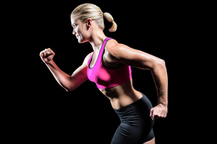 Muscular woman running in sportswear FYI00486084