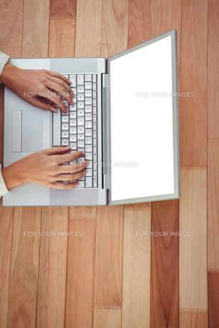 Cropped image of woman using laptop FYI00486232