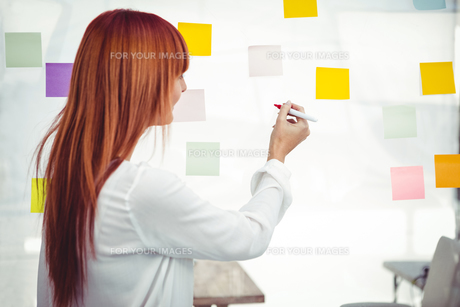 Attractive hipster woman writing on sticky notes FYI00486244