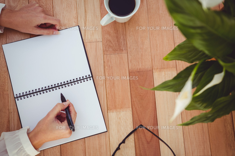 Cropped image of woman writing on notepad FYI00486245