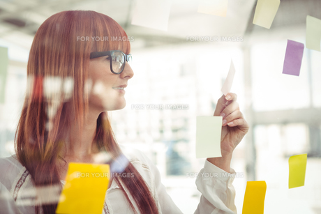 Attractive hipster woman looking at sticky notes FYI00486248