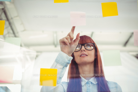 Attractive hipster woman pointing sticky notes FYI00486251