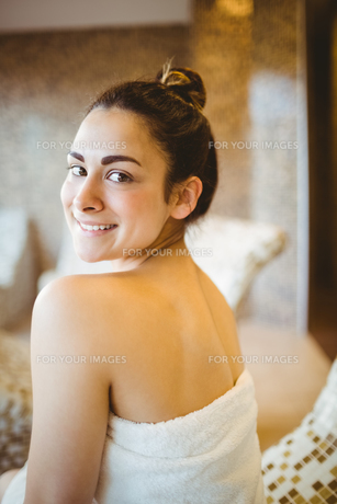 Woman sitting down wearing a towel FYI00486350