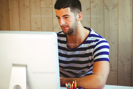 Handsome hipster working at desk FYI00486409