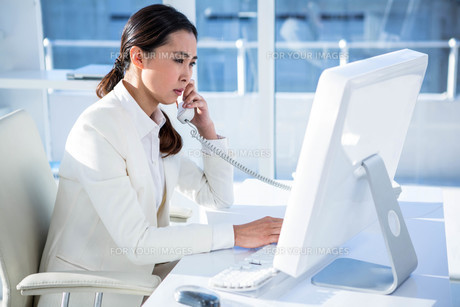 Smiling businesswoman using computer and telephone FYI00486438