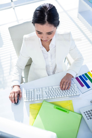 Businesswoman using her pc with documents FYI00486443