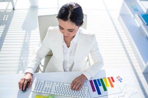 Businesswoman using her pc with documents FYI00486444