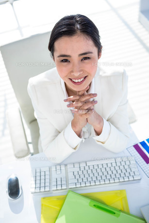 Businesswoman using her pc with documents FYI00486445