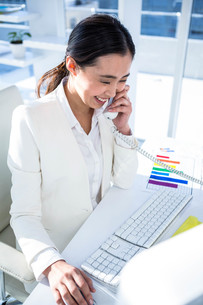 Businesswoman using her pc with documents FYI00486457
