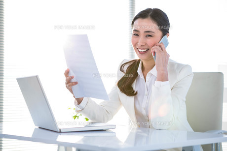 Smiling businesswoman with document phoning FYI00486462