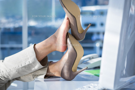 Businesswoman with her legs on her desk FYI00486467