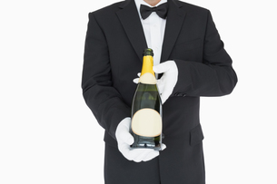 Waiter holding champagne bottle FYI00486543