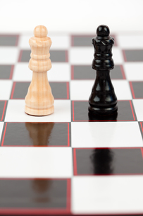 Black and white queen standing at the chessboard FYI00486675