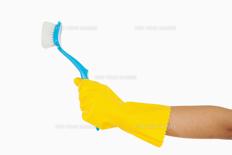 Womans hand holding scrubbing brush FYI00486722