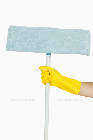 Female hand in glove holding mop FYI00486724
