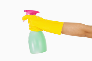 Woman in yellow rubber gloves holding window cleaner FYI00486739