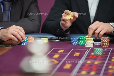 Two men placing roulette bets FYI00486758