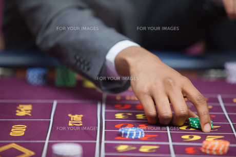Man in casino placing bet FYI00486761