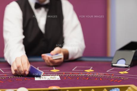 Dealer dealing cards in a casino FYI00486765