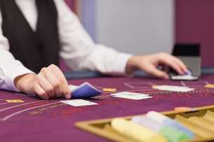 Dealer distributing cards at table FYI00486771