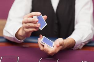 Dealer shuffling deck of cards in a casino FYI00486773