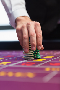 Dealer placing chips on table FYI00486777