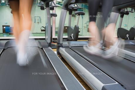 Two people running on treadmills FYI00486868