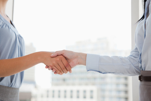 Two women shaking hands in the office FYI00487073