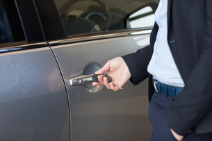 Man opening a car door with a key FYI00487096