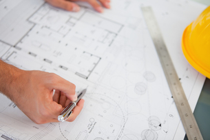 Close up of blueprints with a person making adjustments FYI00487118