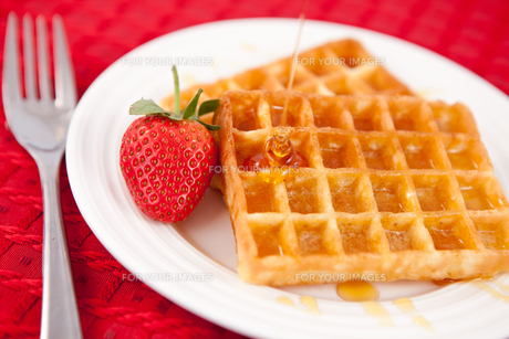 Waffles and syrup and strawberry together in a white plate FYI00487156