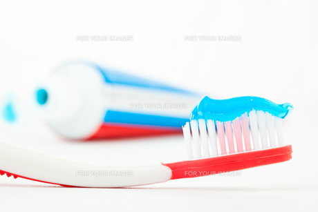 Tube of toothpaste next to a red toothbrush FYI00487181
