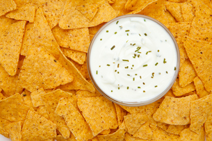 Bowl of dip with herbs surrounded by nachos FYI00487229