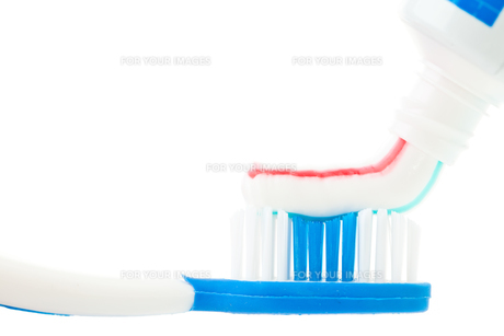 Close up of a tube of toothpaste with a toothbrush FYI00487275