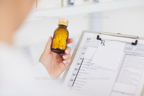 Pharmacist holding a drug bottle and a clipboard FYI00487292