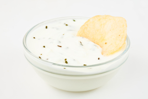 Bowl of white dip with herbs and a nacho dipped in it FYI00487452