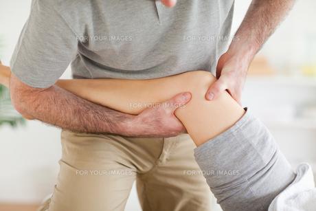 Chiropractor massaging a patients knee FYI00487527