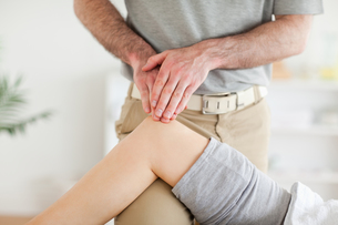 Chiropractor massaging a cute womans knee FYI00487544
