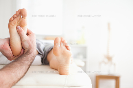 Male masseur doing a reflexology massage FYI00487587