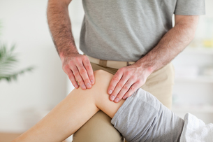 Male Chiropractor massaging a charming womans knee FYI00487593