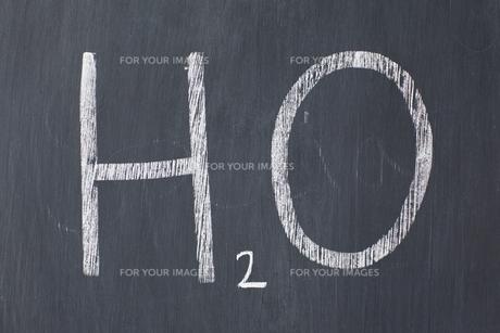 Chemical symbol for water written on a blackboard FYI00487722