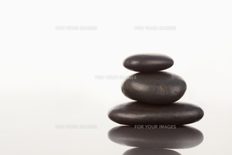 Black pebbles stack on a mirror FYI00487747